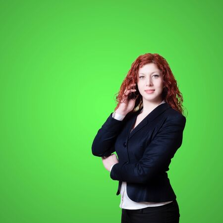 long red hair businesswoman on the phone on green background Stock Photo - 18661692