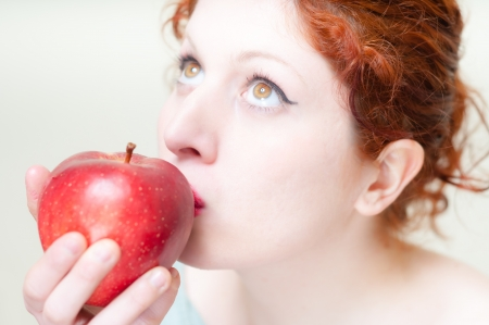 beautiful red hair and lips girl kissing apple on white background photo