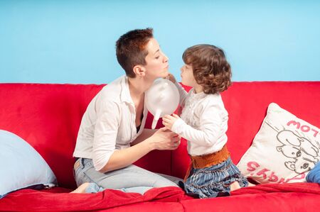 caresses: mother and little daughter hugging on the couch in the living room