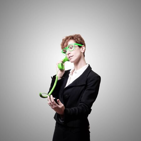 business woman with phone on gray background photo