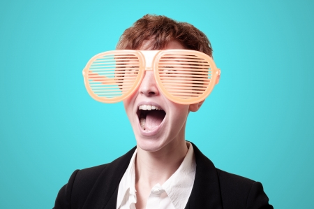 tailleur: businesswoman with big funny eyeglasses screaming on blue background