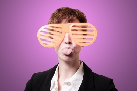 tailleur: businesswoman with big funny eyeglasses and tongue out on pink background