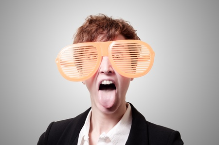 tailleur: businesswoman with big funny eyeglasses and tongue out on gray background Stock Photo