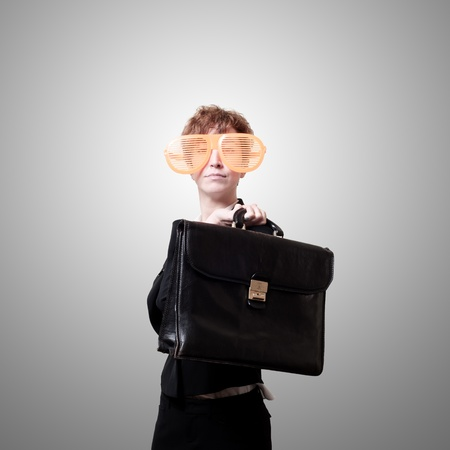 tailleur: businesswoman with big funny eyeglasses and briefcase on gray background Stock Photo