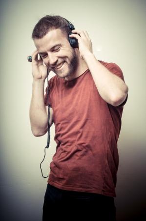 audifonos: retrato de la vendimia de moda hombre sonriente con auriculares en fondo gris