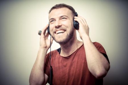 escuchando musica: retrato de la vendimia de moda hombre sonriente con auriculares en fondo gris