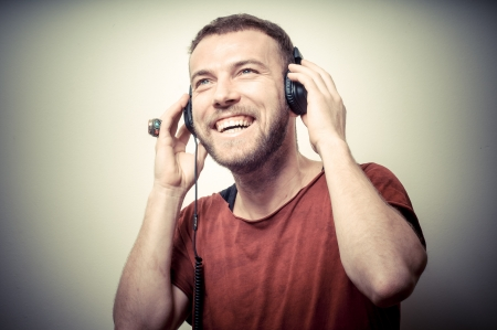 listening music: vintage portrait of fashion smiling guy with headphones on gray background