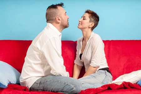 caresses: husband and wife hugging on the couch in the living room
