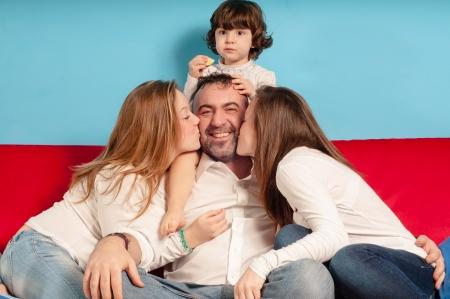 papa y mama: feliz padre e hijas en el sof� de la sala de estar