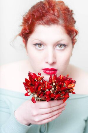 beautiful red hair and lips girl with red chillies on white background photo