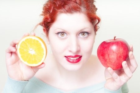 beautiful red hair and lips girl with orange and apple on white background photo
