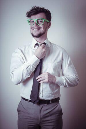 Sexy stylish businessman adjusting tie on gray background Stock Photo - 18823153