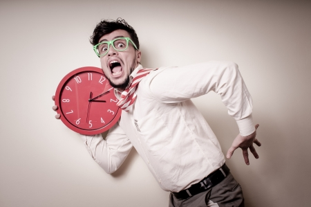 against the clock: funny businessman with wall clock on gray background