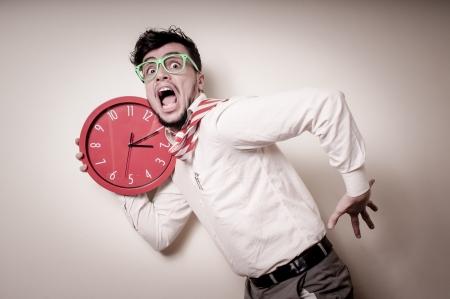 orologio da parete: uomo d'affari divertente con orologio da parete su sfondo grigio Archivio Fotografico