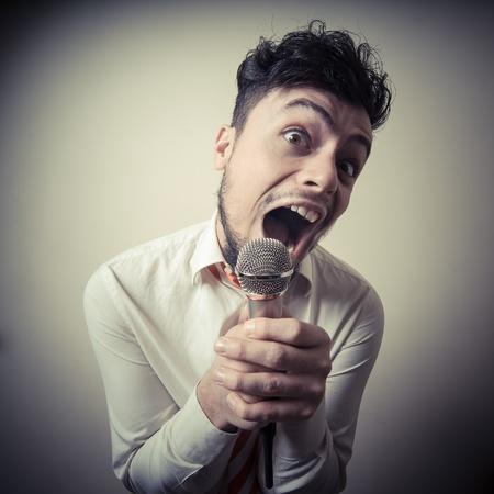 beaty: funny stylish businessman singing on gray background