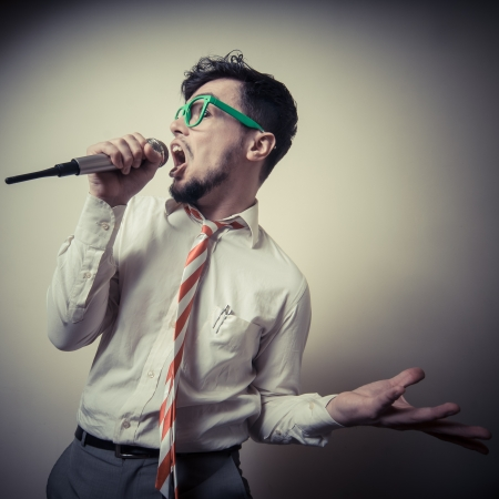 funny stylish businessman singing on gray background photo