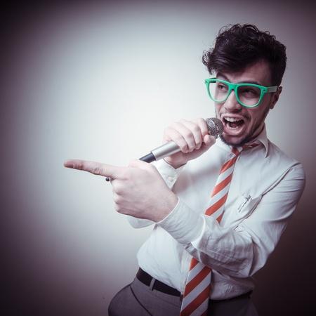 funny stylish businessman singing on gray background
