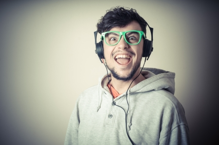 boy with sweatshirt and headphones on gray background