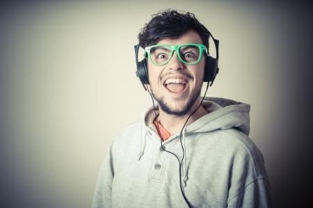 audifonos: chico con camiseta y auriculares sobre fondo gris