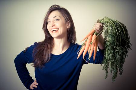 beautiful woman with carrots on gray background photo