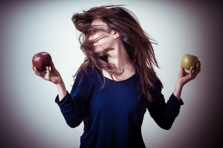 beautiful woman choosing red or yellow apples on gray background photo