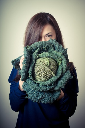 savoy: beautiful woman with savoy cabbage on gray background