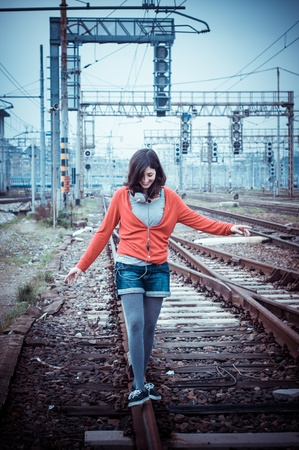 beautiful stylish woman listening to music in railway photo