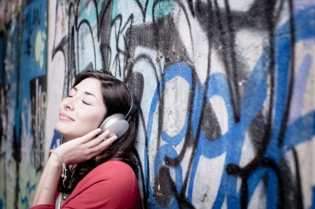 Beautiful stylish woman listening to music in the street  photo