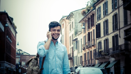 stylish man in the street at the phone in the city