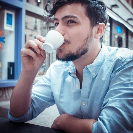 stylish man drinking a coffee at the bar in the city photo