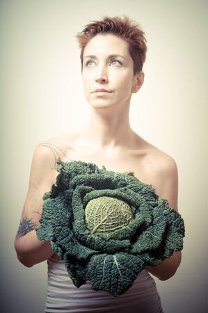 beautiful girl with short red hair and vegetable on gray background photo