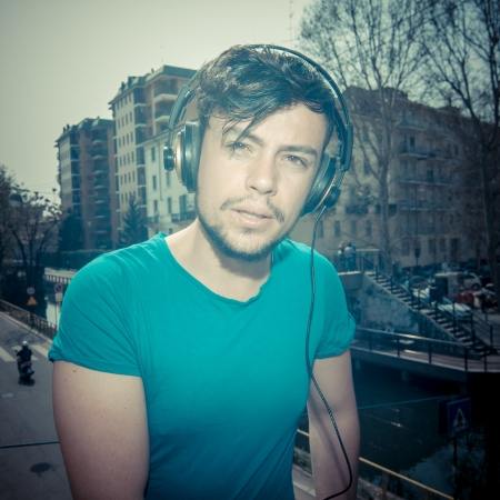 young man hipster listening to music with headphones photo