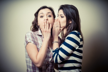 gossip: two young woman gossiping on vignetting background
