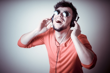 Stylish man listening to music on vignetting background photo
