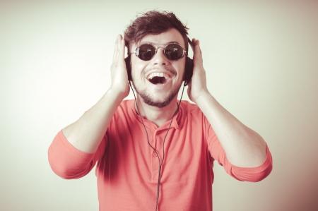 Stylish man listening to music on vignetting background photo