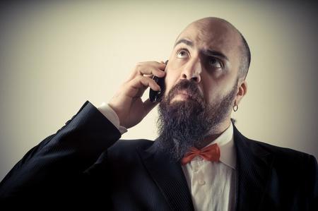 bärtiger mann: lustig elegant b?rtiger Mann am Telefon auf Vignettierung Hintergrund