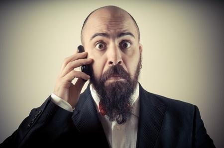 hombre con barba: divertido hombre barbudo elegante en el tel?fono en el fondo vi?etas Foto de archivo