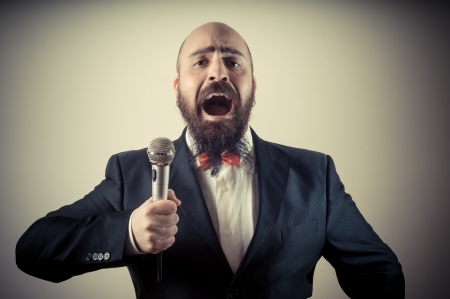 funny elegant singer bearded on vignetting background