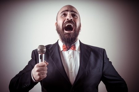 bald ugly:  funny elegant singer bearded on vignetting background