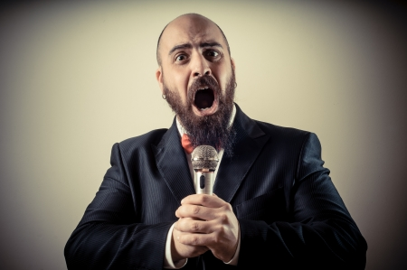 funny elegant singer bearded on vignetting background photo
