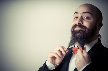 bald ugly:  funny elegant bearded man touching beard on vignetting background