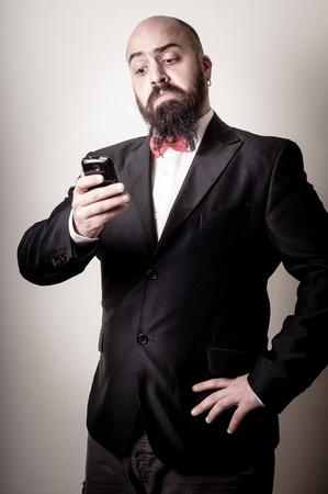 hombre con barba: divertido hombre barbudo elegante en el tel?no en el fondo vi?s