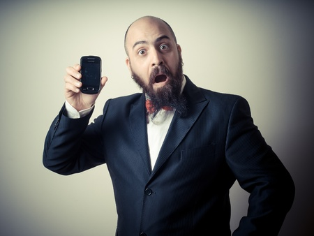 hombre con barba: divertido hombre barbudo elegante que muestra el tel�fono en el fondo vi�etas Foto de archivo