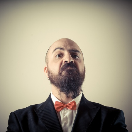 funny elegant bearded man on vignetting background photo