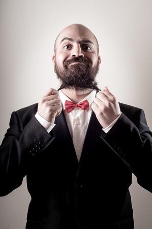 funny bearded man:  funny elegant bearded man touching beard on vignetting background