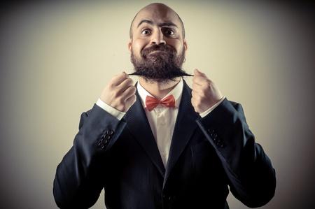 funny elegant bearded man touching beard on vignetting background photo