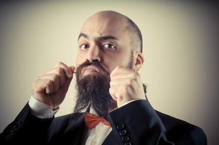 hombre con barba: divertido hombre barbudo elegante tocar bigote en vi?etas de fondo Foto de archivo