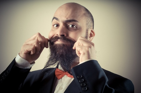 funny elegant bearded man touching mustache on vignetting background photo