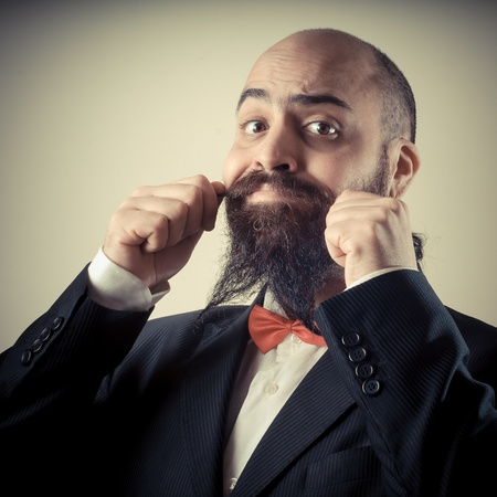 bald ugly:  funny elegant bearded man touching mustache on vignetting background