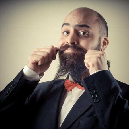 bärtiger mann: lustig eleganten b�rtigen Mann ber�hren Schnurrbart auf Vignettierung Hintergrund